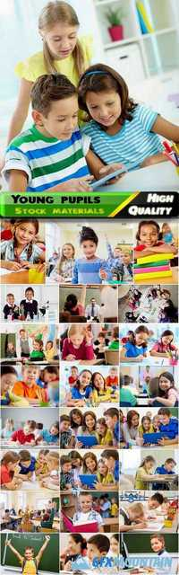 Students of the lower grades in the classroom with a teacher studying different science and lessons, kids, children, educational Stock images